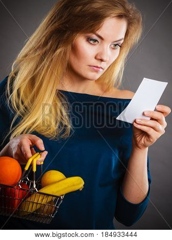 Worried Woman Holding Shopping Basket With Fruits