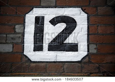 Number twelve hand painted on plaster background