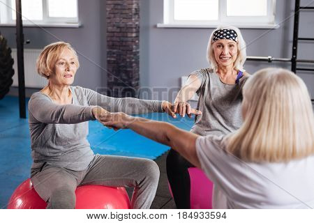 Fitness class. Pleasant friendly senior women sitting in a circle and holding their hands together while having a fitness class
