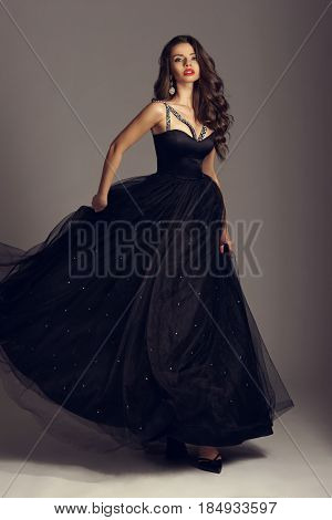 Young beautiful woman standing and posing in black ball gown on white gray background. Fashion style portrait of girl with long curly brunette hair