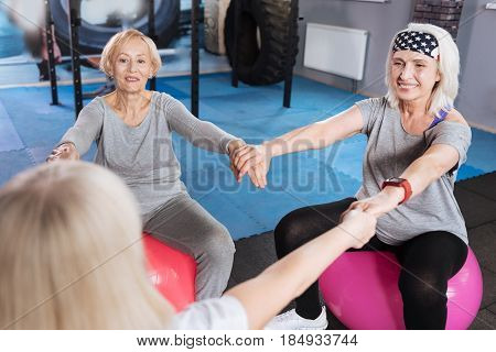 Being together. Happy delighted nice women looking at their friend and smiling while sitting together in the circle