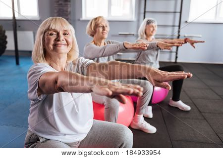 Fitness exercise. Happy nice elderly woman sitting on the fitness ball and having her hands in front of her while enjoying this fitness exercise