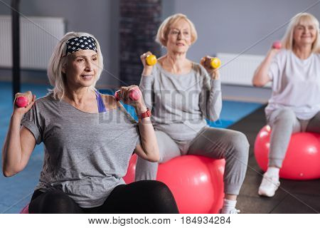 Fitness equipment. Confident persistent nice women sitting on fitness balls and exercising with dumbbells while visiting a fitness club