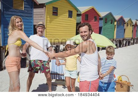 Portrait of multi-generated family holding hands at beach during sunny day
