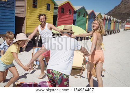 Happy multi-generated family playing at beach during sunny day