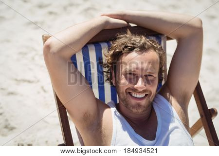 High angle portrait of young woman relaxaing on lounge chair at beach during sunny day