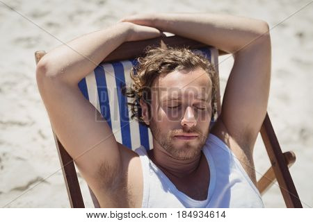 High angle view of young woman relaxaing on lounge chair at beach during sunny day