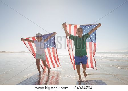 Siblings holding American flags while running on shore at beach during sunny day