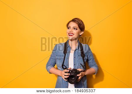 Young Fashionable Female Photographer Is Smiling On The Yellow Background. She Is Excited And Holdin