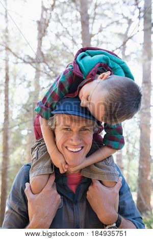 Portrait of happy mature father carrying son on shoulders in forest