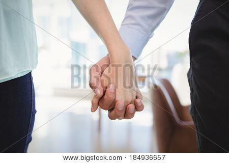 Mid section of couple standing with hand in hand in office