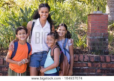 Portrait of happy teacher with students standing at nature reserve during field trip