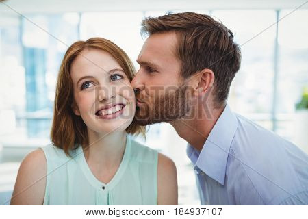 Affectionate man kissing woman in office