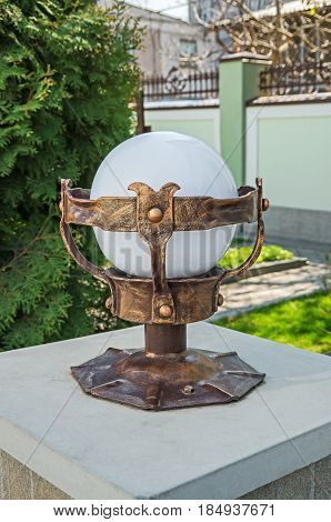 A spherical street lamp in a forged garment which is installed near the entrance doors or adorns the infield