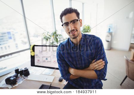 Portrait of graphic designer standing with arms crossed at desk in office