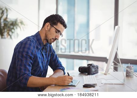 Graphic designer using graphic tablet at desk in office