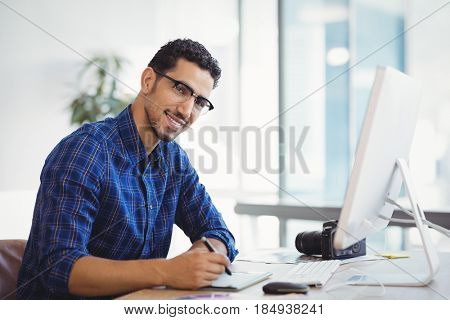 Portrait of smiling graphic designer using graphic tablet at desk in office
