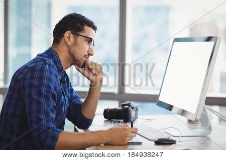 Attentive graphic designer using graphic tablet at desk in office