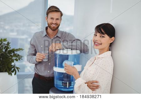 Portrait of smiling executives holding glasses of water in office
