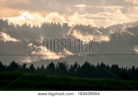 Green landscape and foggy mountain forest. Fantastic forest landscape. Beautiful clouds. Dark forest in a haze landscape.