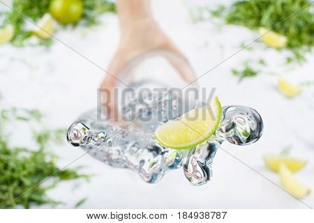 Fresh Lime In Glass With Water Splash Over White Background. Greens And Slices Of Lime In The Backgr