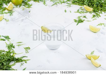 Fresh Limes In The Water On A White Background. Greens And Slices Of Lime In The Background. A Glass