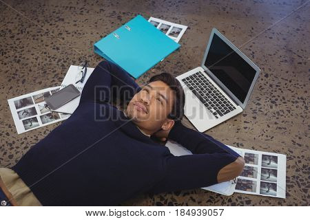 Thoughtful businessman lying by laptop and photographs on floor at office