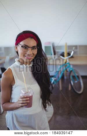 Portrait of happy businesswoman holding drink in disposable glass at office