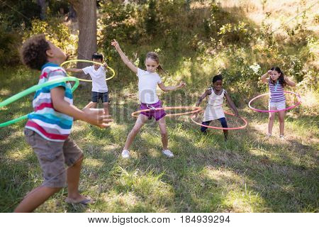 Cheerful friends playing with hula hoops on grassy field at campsite