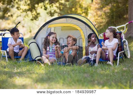 Group of happy friends eating candies while sitting outside tent at campsite