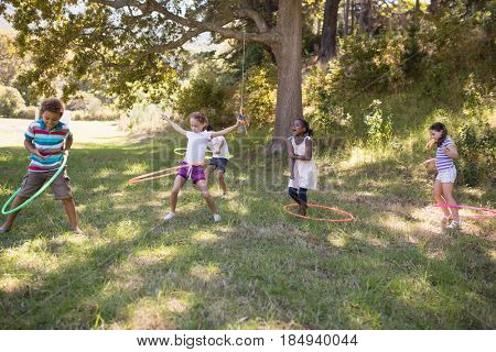 Group of friends playing with hula hoops on grassy field at campsite