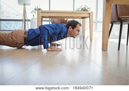 Determined executive doing push-ups in office