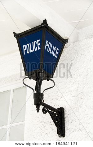 Traditional blue police lamp outside police station
