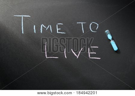 Conceptual chalk on a dark slate time to live and hourglass
