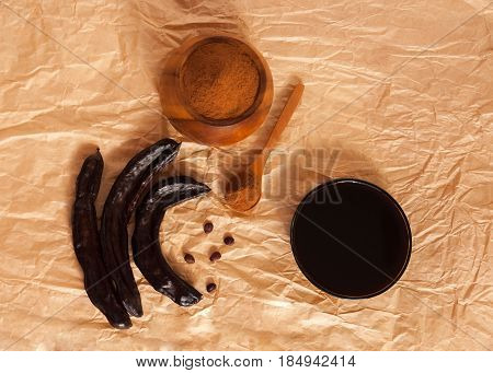 carob pods with seeds pekmez sirop and without gluten carob pod's flour on the paper background