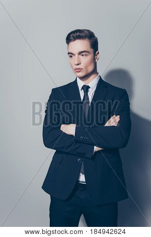 Young Attractive Businessman Is Standing On The Pure Light Background. He Looks Stunning! So Severe