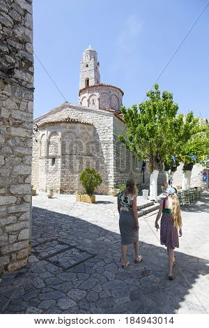 areopoli, greece, 25 april 2017: tourists walk the ancient streets of areopolis in greece on mani peninsula of peloponnese with old church tower in the background