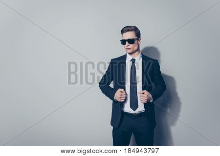 Portrait Of Attractive Businessman In Sungllasses. He Is Standing On The Pure Light Background. He L
