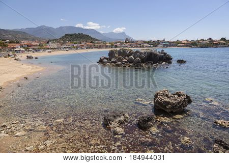 beautiful sandy beach of Stoupa in greece on sunny day in spring on peloponnese with mountains in the background