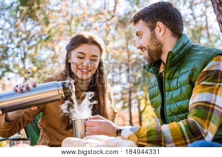 Smiling Woman Pouring Tea From Thermos
