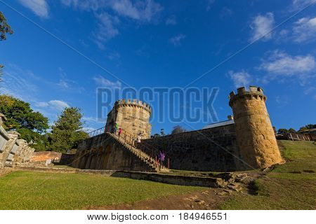 Tasmania, Australia - April 12, 2017 : Tourists walking up to Guard Tower on Settlement Hill at Port Arthur Historic site in Tasmania, Australia on April 12, 2017. Built in 1842 as military precinct