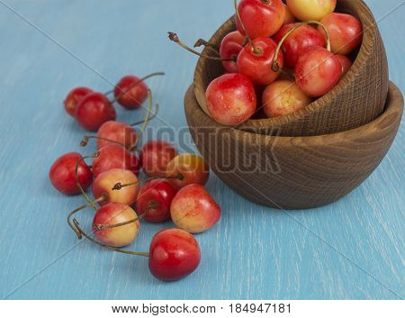 Background of ripe cherries. Pile of fresh and tasty cherries in wooden bowl. Fresh cherries scattered on a wooden table.