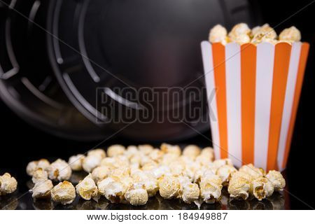 Popcorn and a movie role in front of black background concept cinema and theater