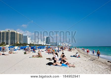 MIAMI BEACH FLORIDA - FEBRUARY 15 2017: Tourists sunbath swim and play on South Beach in Miami Beach Florida USA on February 15 2017.