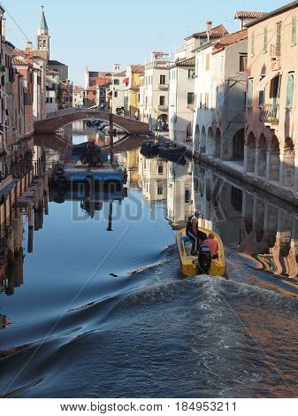 Chioggia, Italy, A motor boat sails in a canal and leaves the trail in the water
