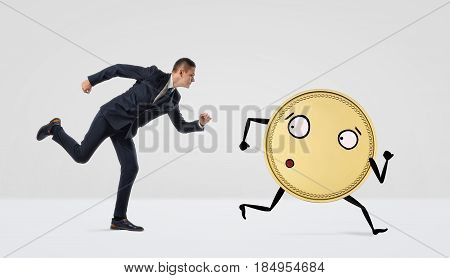 A businessman running after a golden coin with arms and legs on white background. Business marathon. Working for profit. Money race.