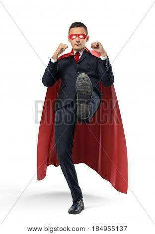 A businessman in a red superhero cape kicking an invisible object on white background. Business and competition. Adversaries. Fighting off problems.