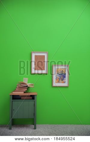 Bedside table with books and paintings on greenery wall background