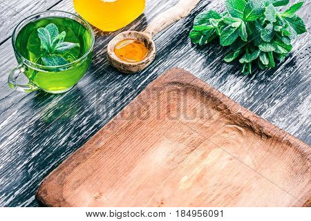 Green mint tea in translucent glass tea cup with honey and fresh mint leaves on textured black wood background with rustic wooden plate