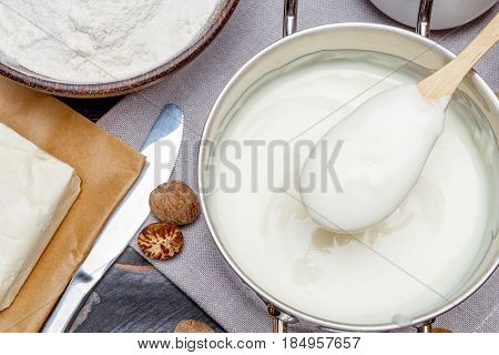Preparation of bechamel sauce in a pan and ingredients on the wooden table